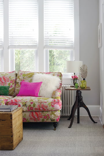 A TV room combines a Manuel Canovas floral on the sofa with a plaid rug from Stark. © Abby Greenawalt