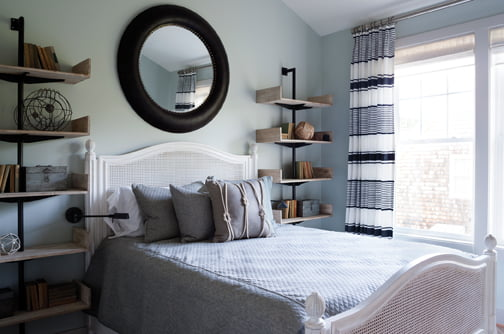 Combined with black-and-white Ralph Lauren drapes, a white-painted wicker bedstead creates a crisp, welcoming vibe.