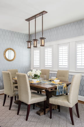 Contemporary wallpaper in a leaf pattern offsets a dining room's original light fixture.