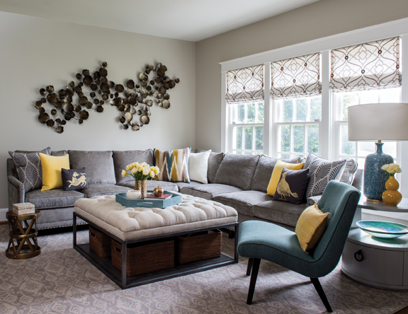 Yellow and teal accents, as well as an intriguing metallic wall sculpture, enliven the neutral family room.