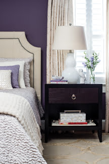 Eggplant-hued walls add warmth to the master bedroom; the headboard and accents are white for balance.