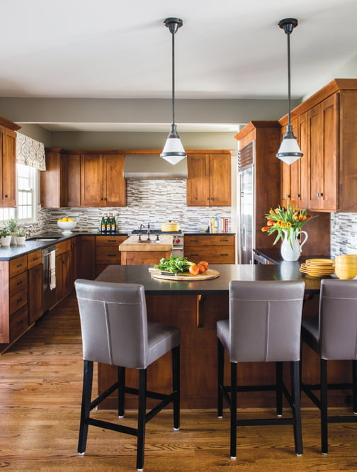 In the kitchen, contemporary pendants and  a glass-tile backsplash create a fresh, new look.