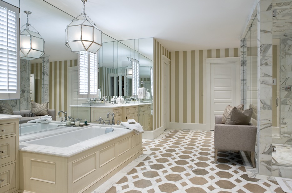 Lighter marble tops the Wood-Mode vanities and tub surround. The fixture is by Circa Lighting.