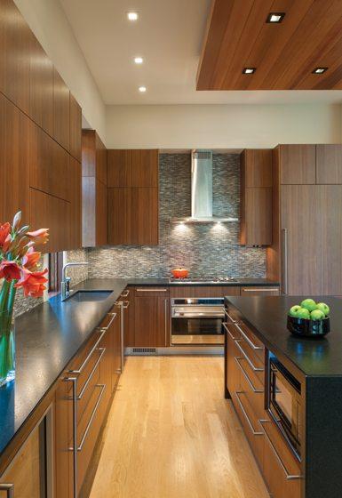 The kitchen combines Poggenpohl cabinets, granite countertops and a glass-tile backsplash.