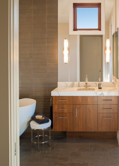 The master bath boasts a sculptural tub by Kohler and a marble-topped vanity.