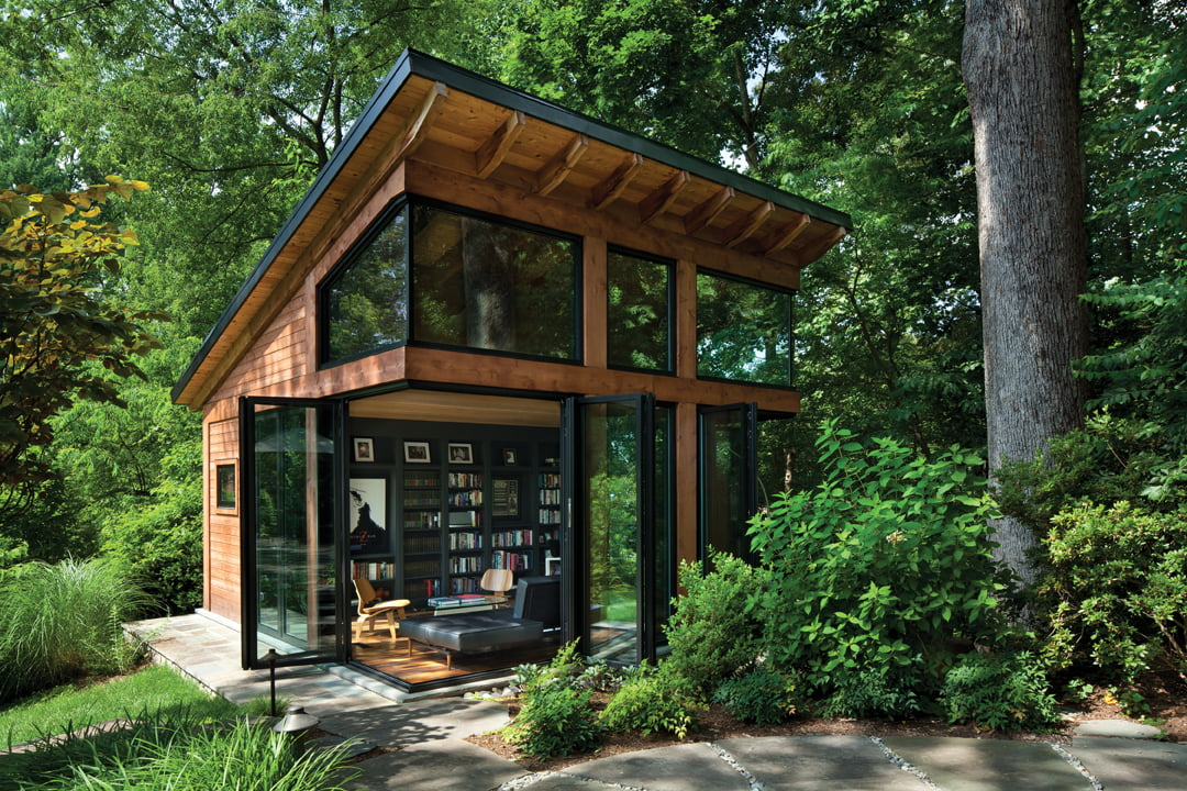 Doors and a NanaWall system  open the cedar-clad structure to the outdoors.