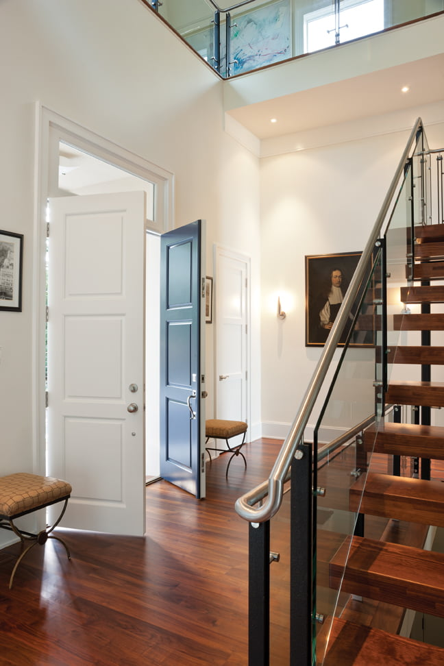 The entry opens to a hallway boasting walnut floors and a stairwell made of pine blocks, glass and steel.