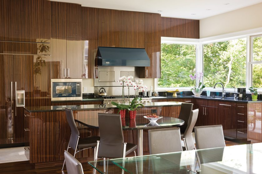 The kitchen features striking, strong-grained macassar cabinetry and a table by the island for casual meals.