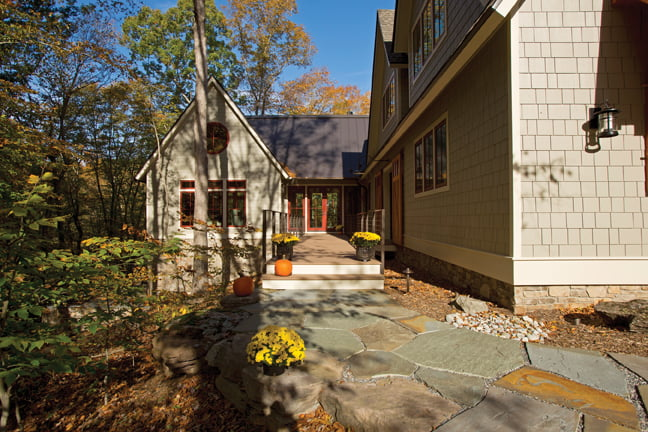 Flagstone paving and a dock-like walkway lead to the front entry;  the music room occupies the wing on the left.