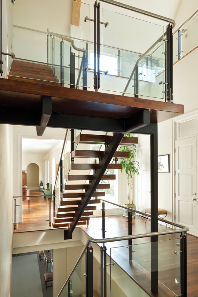 From the front hall, stairs lead down to the lower level and up to the husband's office.