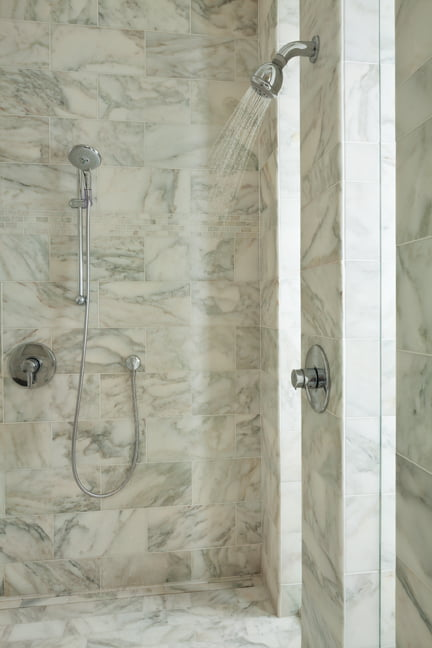 The shower is clad in Calacatta marble.