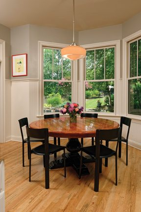 At the far end of the room, a bay window offers views of the blooming backyard.