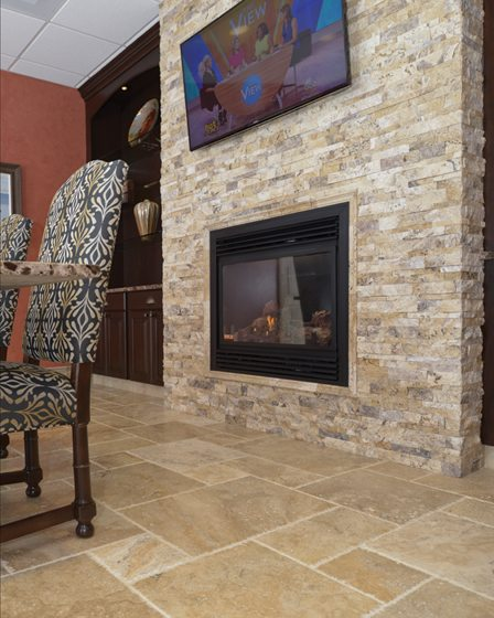 An accent wall of rustic stone turns a fireplace and TV into a focal point.