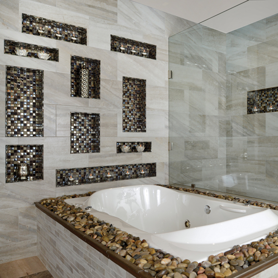 A stone tub deck and glass mosaic wall niches dress up a spa bath clad in porcelain tile.