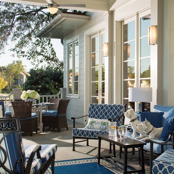 Kingsley-Bate chairs are paired with a vintage McGuire dining table on the porch.