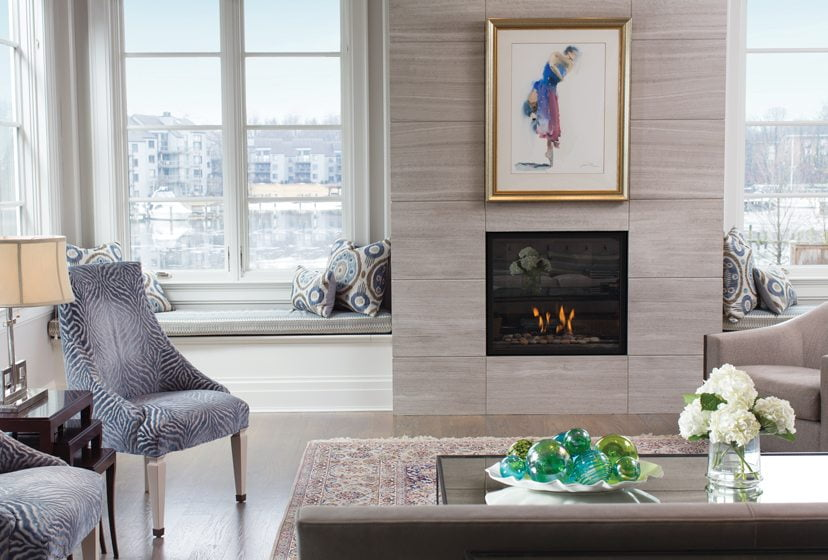 The fireplace in the living room is flanked by views of the creek.