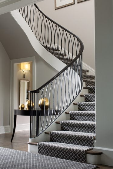 A gracefully curved stair creates drama in the front entry.