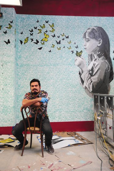 Yescka poses at Espita Mezcaleria against the backdrop of his mural.