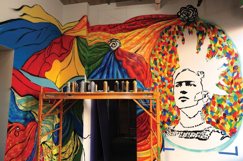 Colorful textiles and a soon-to-be-finished portrait of Frida Kahlo celebrate Mexican culture.