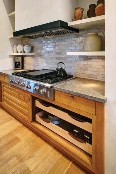 Under the cooktop, sliding doors open to pot-and-pan storage without blocking the passageway.
