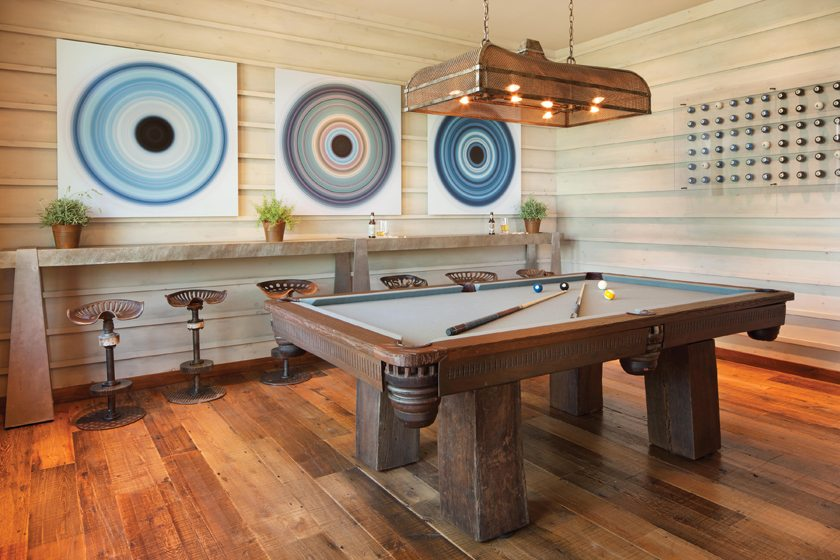 In the billiard room, Swatchroom created the 3D walls and fashioned stools from tractor seats.