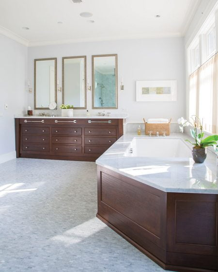 The floor and shower interior in the master bath are clad in marble tile from Waterworks.