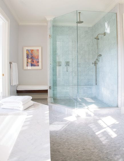 A glass-enclosed shower lets light filter through the luxurious space.