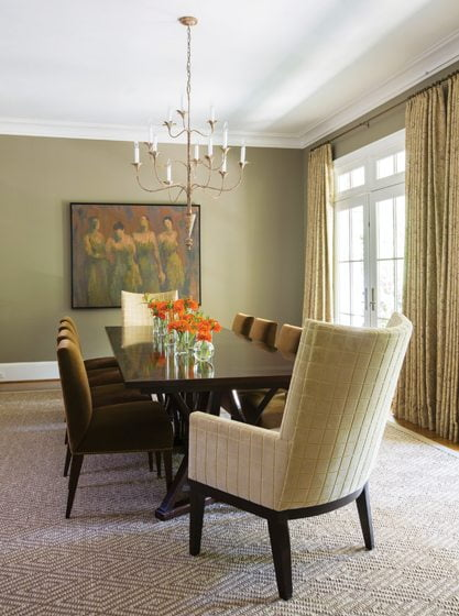 The dining room houses a Stark rug, a David Iatesta chandelier and a painting by Chris Chernow .