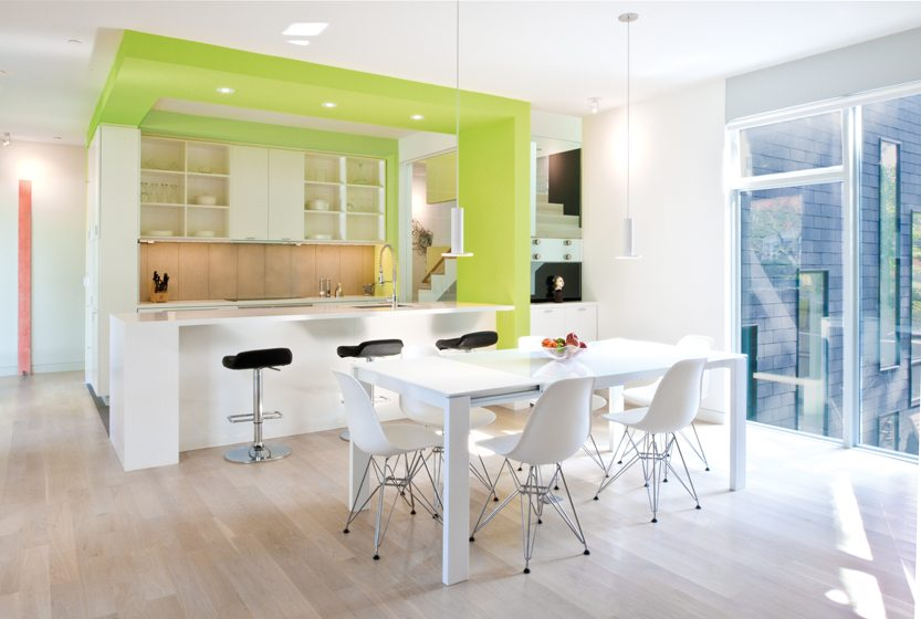The galley kitchen is adjacent to the dining area, with Eames-designed chairs and a Ligne Roset table.