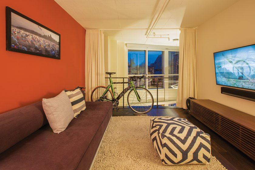 An accent wall in the guest room is clad in orange Veneer Emboss wallpaper.