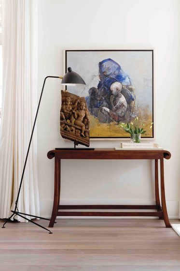 An 18th-century wood carving rests beside a painting by Bangladesh artist Sheikh Afzal Hossain.
