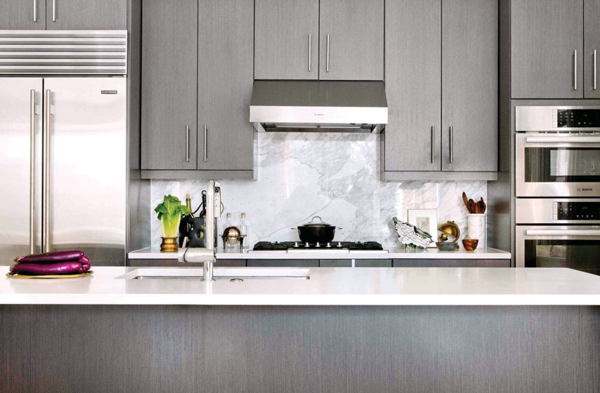 A marble-slab backsplash  adds a timeless touch in the kitchen.