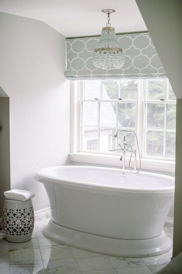 A Currey & Company chandelier hangs over the bathtub.