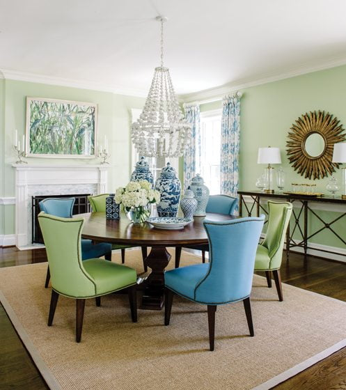 In the dining room by Fiona Weeks, chairs upholstered in bright hues surround the table.