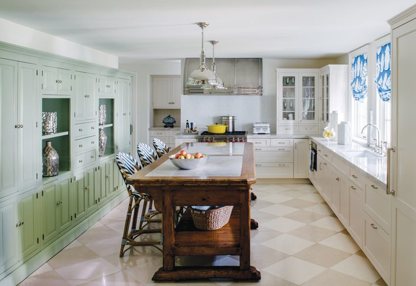 In the kitchen, two-tone, harlequin-laid travertine tile updates the checkerboard floor pattern.