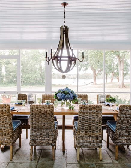 Seen through one of the enfilades, the porch's wood-and-iron chandelier hangs above a rustic table.