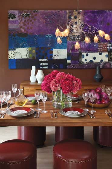 Painted a custom color by Sherwin Williams, the dining room showcases art by Tati Kaupp. © Ron Blunt