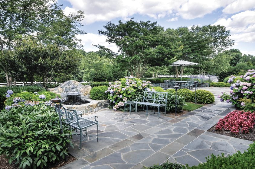 A flagstone terrace is centered by a fountain. © Erin Brooke Bogan and John Spaulding