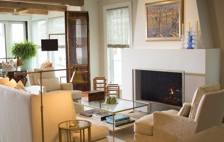Furniture is comfortably grouped around a sculptural fireplace in the living area.
