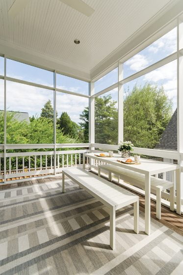 The screened porch was rebuilt and furnished with a table and chairs from Design Within Reach.