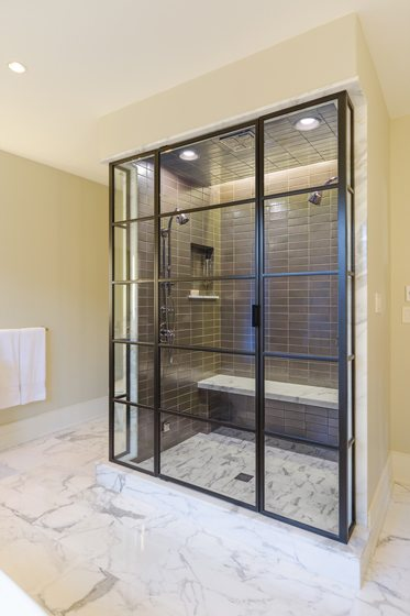 The shower has a metal-and-glass enclosure that matches the home's metal-clad windows.