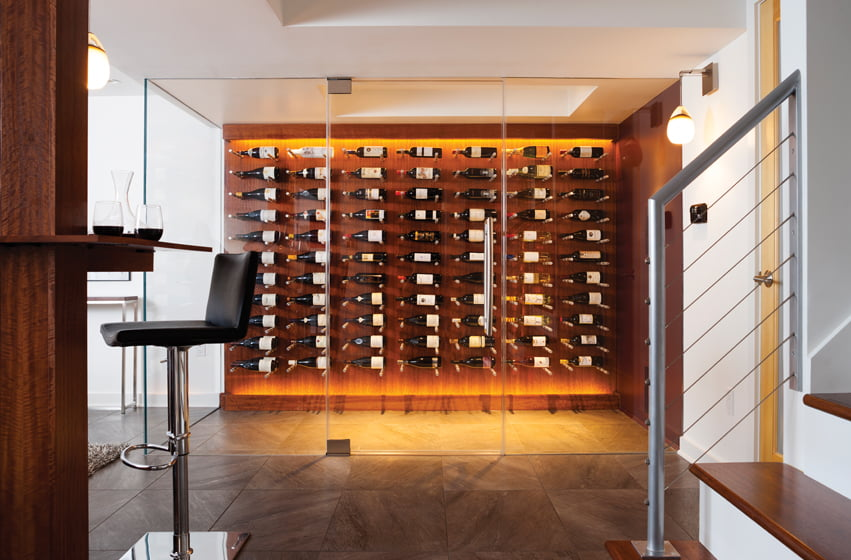 Behind a wall of pane-less glass, the climate-controlled wine room stores about 240 bottles.
