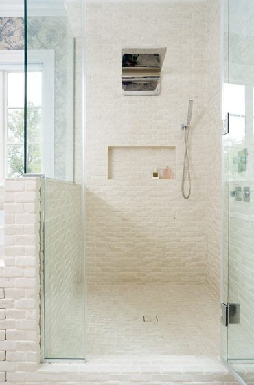 In the master bath, antique tumbled-travertine tile covers the floors and walls.