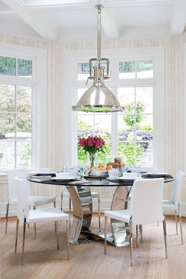 In the breakfast area, a custom table is paired with a light fixture by Eichholtz.