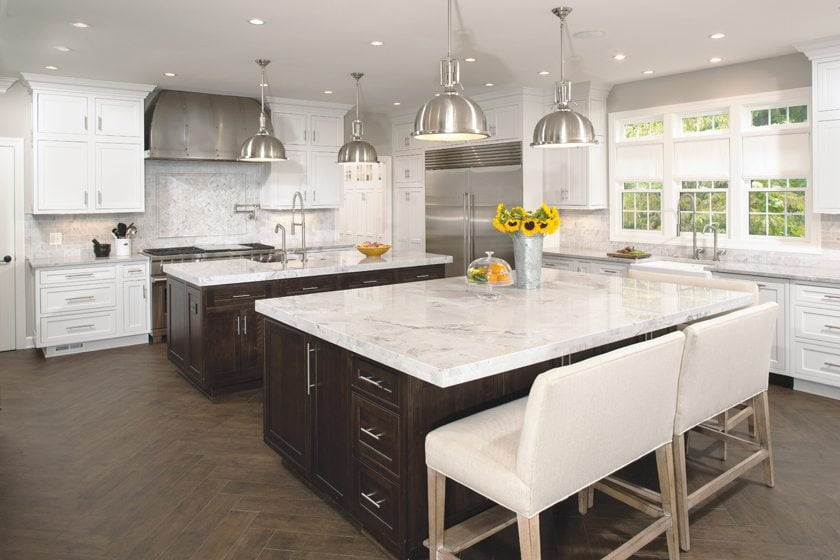 The new kitchen boasts custom cabinetry and two large islands topped with thick quartzite counters.
