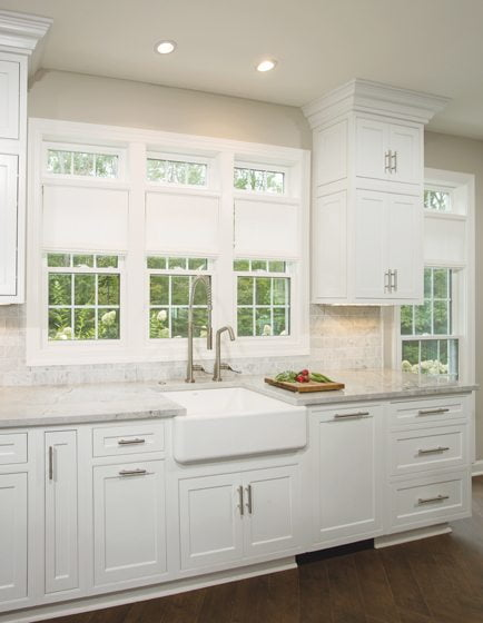 A white porcelain apron sink offers window views.