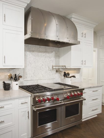 A double-oven Wolf range and custom hood create a focal point against the far wall.