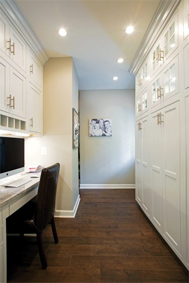 From the kitchen, a hall lined with cabinetry leads to the mudroom.