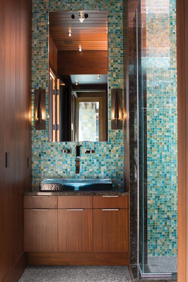 A blue-glass sink is illuminated with LED lights in the pool house bathroom.