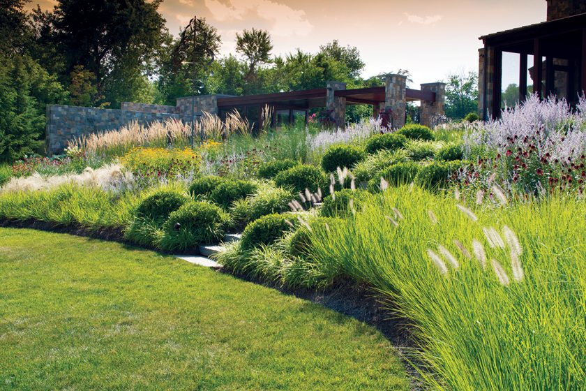 A rich tapestry of perennials and grasses leads down to the water.